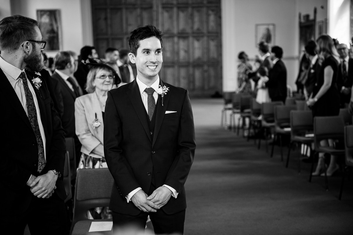 Smiling groom awaits the arrival of the bride at Malvern College In Worcestershire