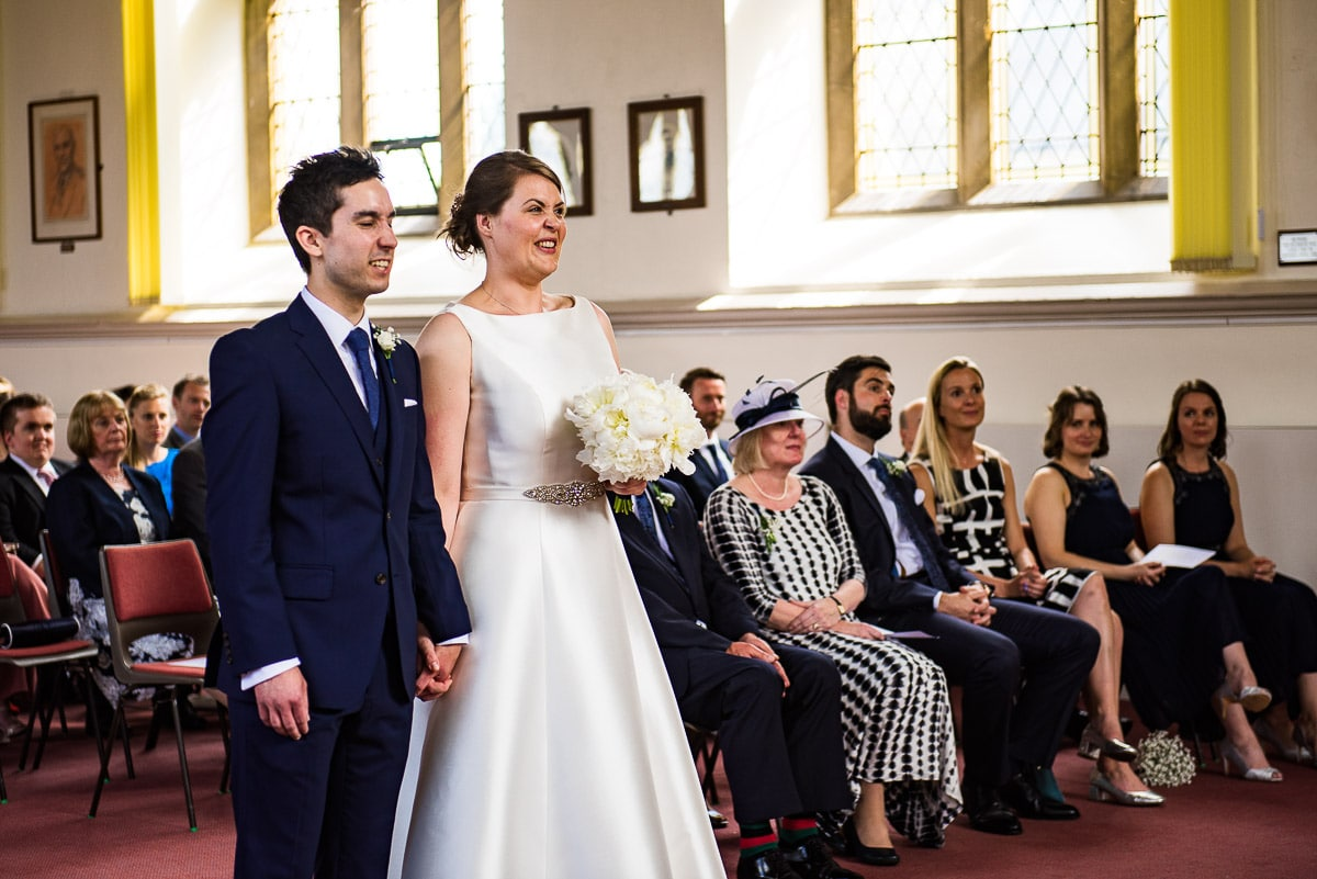 Bride and groom hold hands and pull silly faces as their vows are read