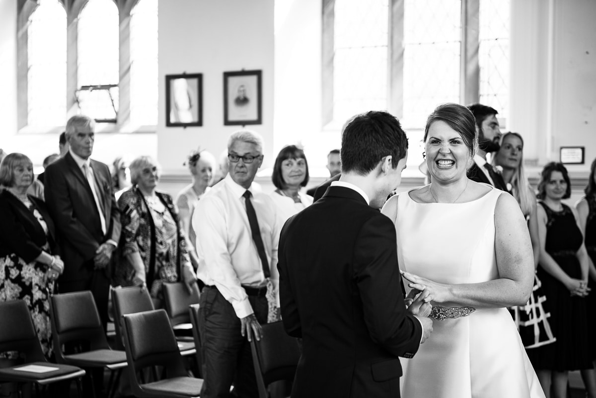 Reportage image of bride grimacing as groom puts on her wedding ring