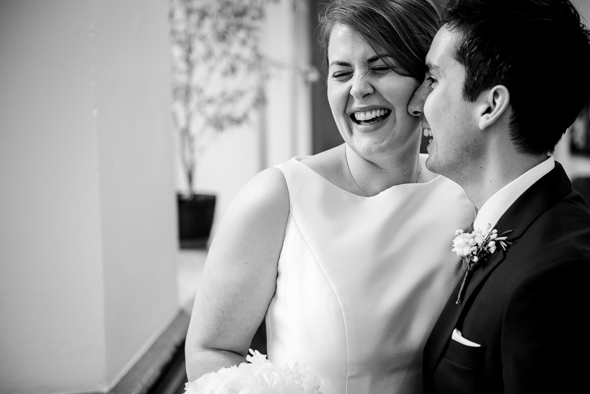 black and white close up portrait of bride and groom laughing with heads together