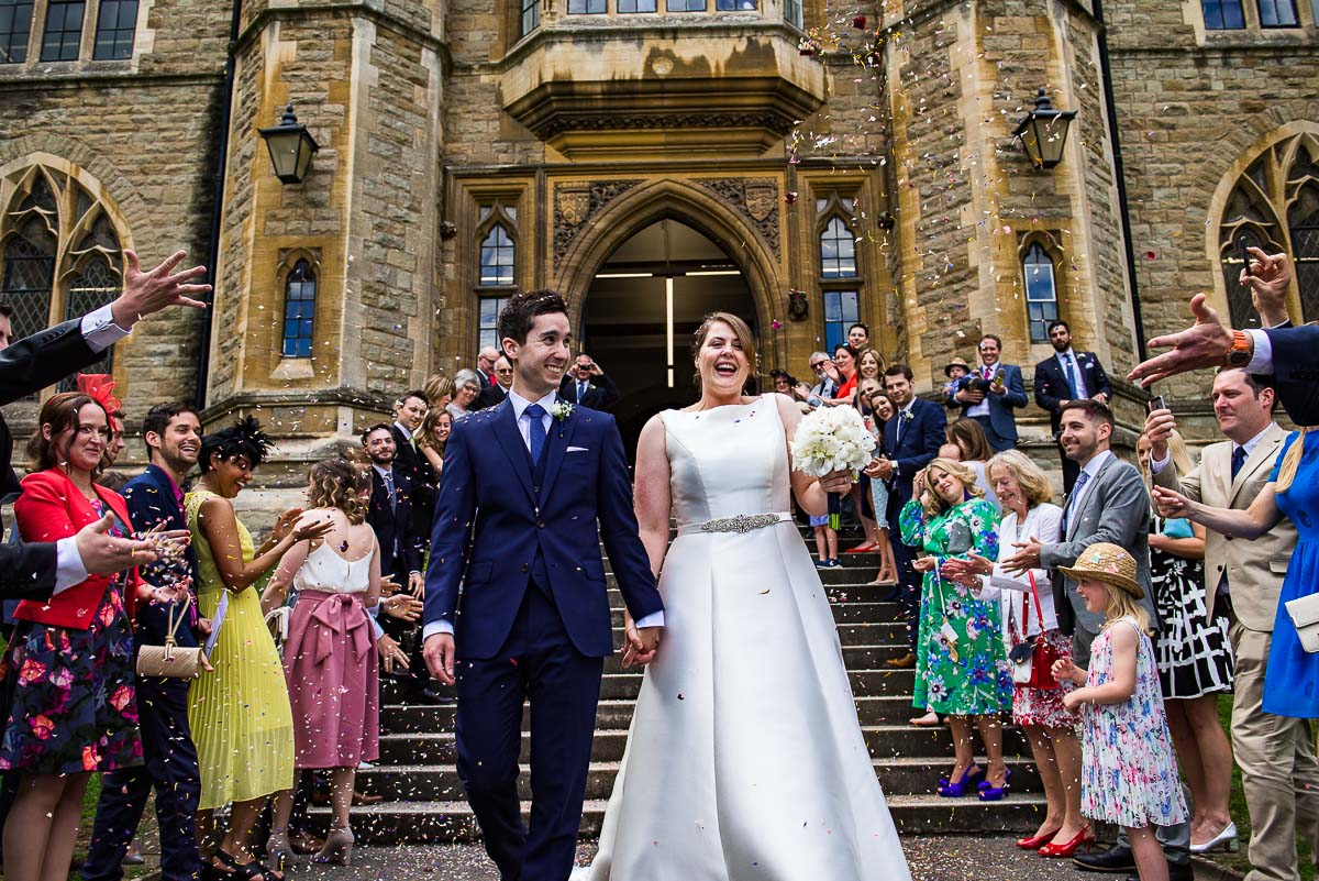 Bride and groom walk down the steps of Malvern college wedding venue as guests throw confetti