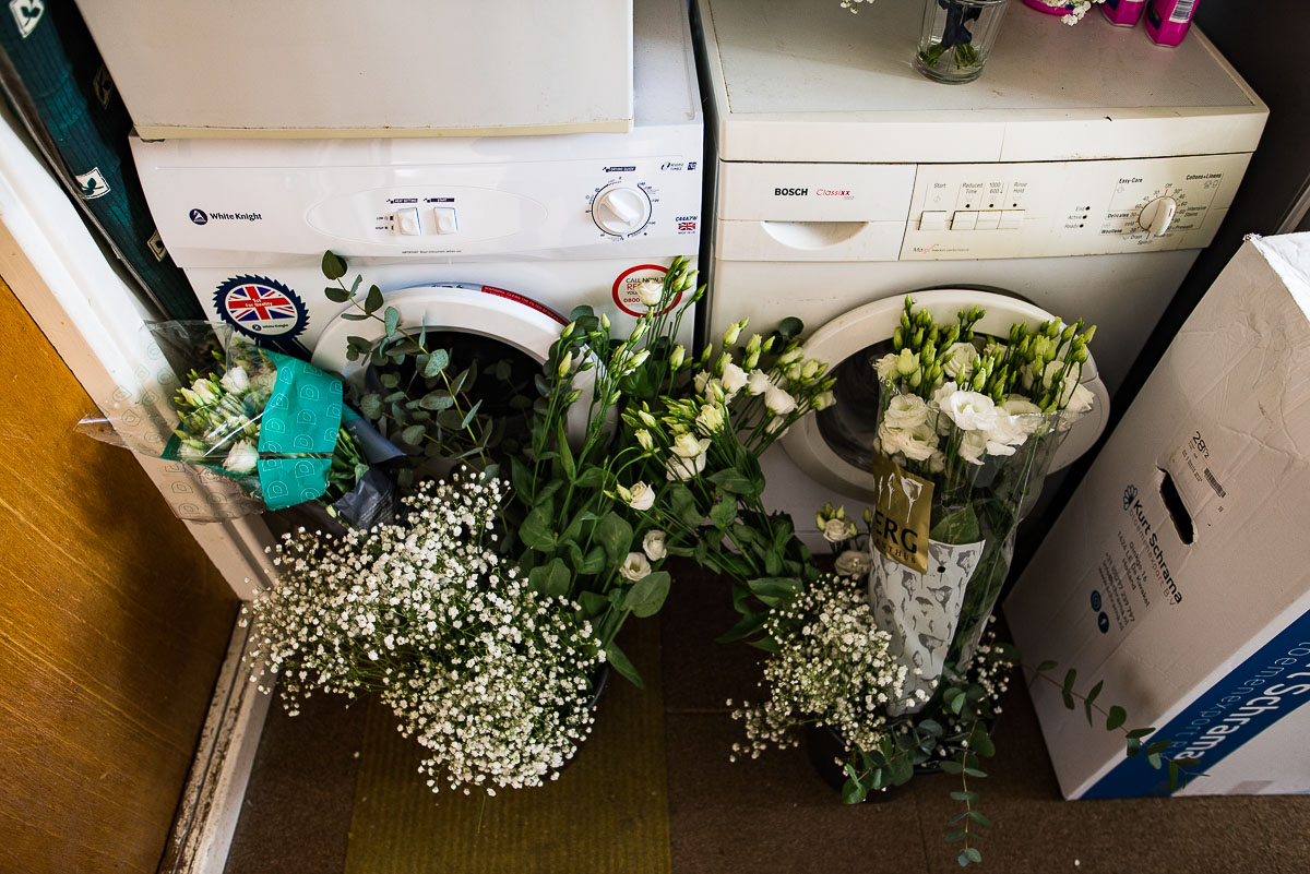 White wedding flowers lent against washing machines