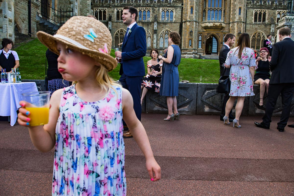 Documentary capture of girl in summer hat and floral dress during wedding reception