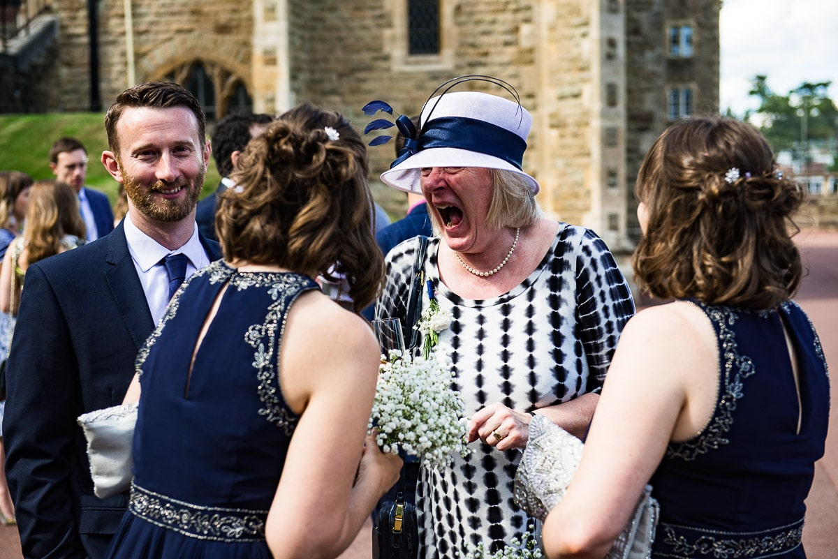 Lady in a wedding hat laughing hysterically with mouth wide open