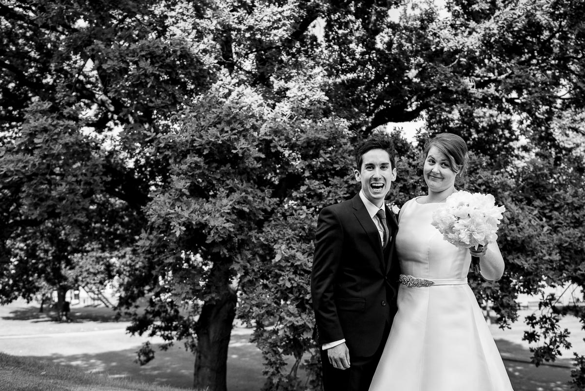 black and white natural portrait of bride and groom having fun in front of tree