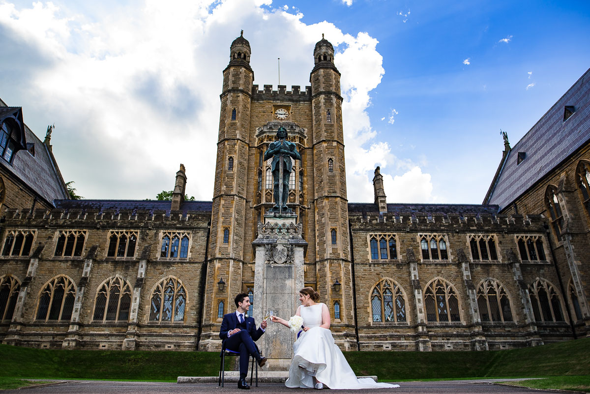 bride and groom toast champagne outside Malvern College chapel