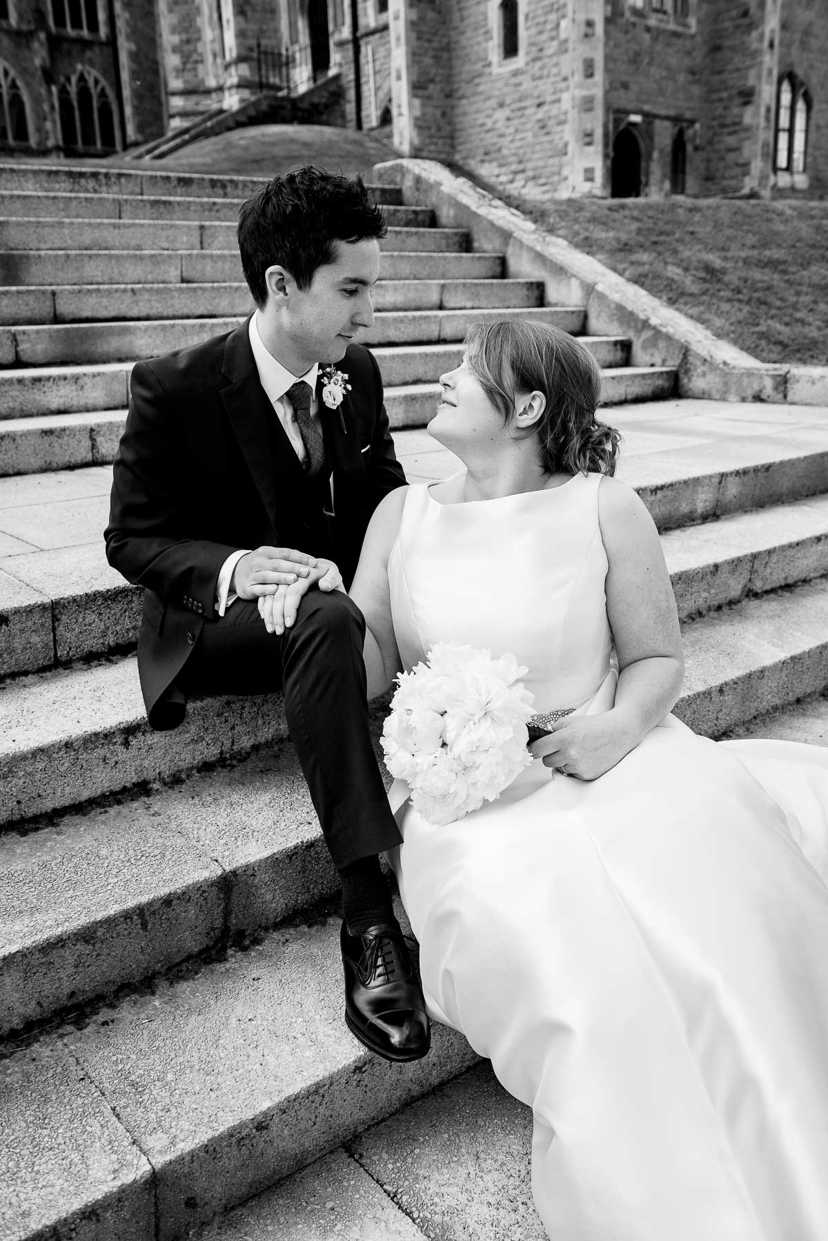 Wedding couple pose on steps in vanity fair style shot of the chapel