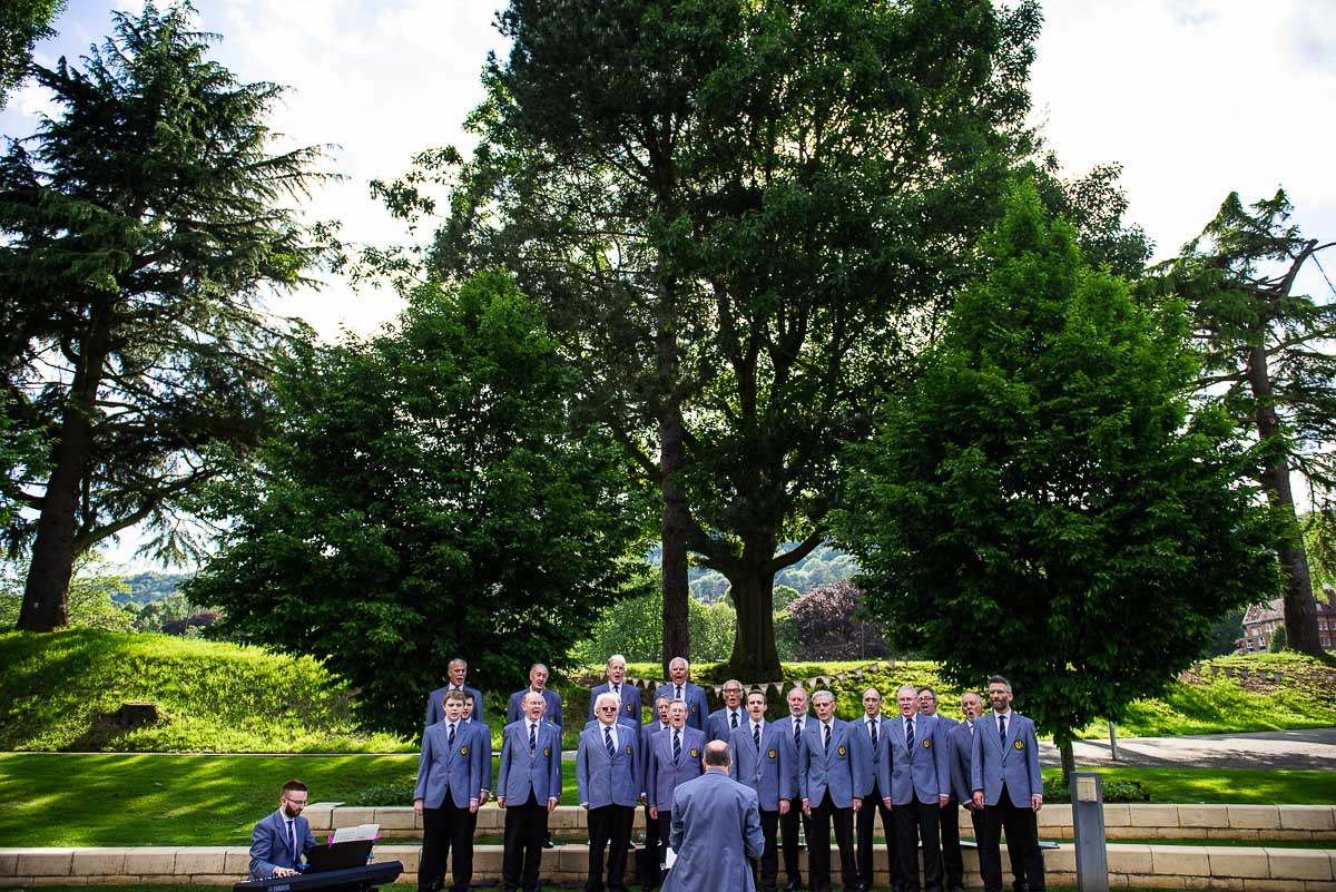 Malvern male choir perform in front of green woodland