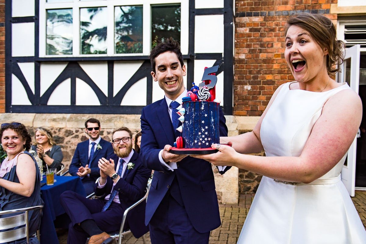bride and groom carrying a fifth birthday cake decorated with captain america figure