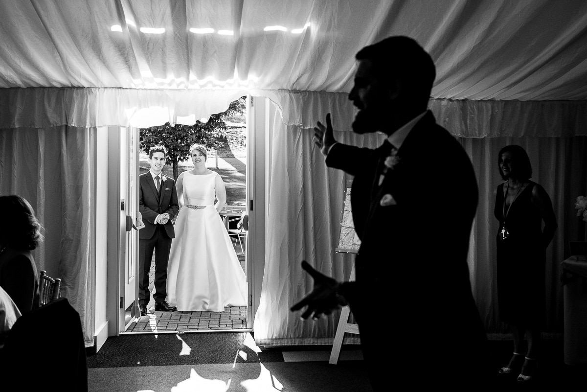 Bride and groom wait to make an entrance as a guest introduces them