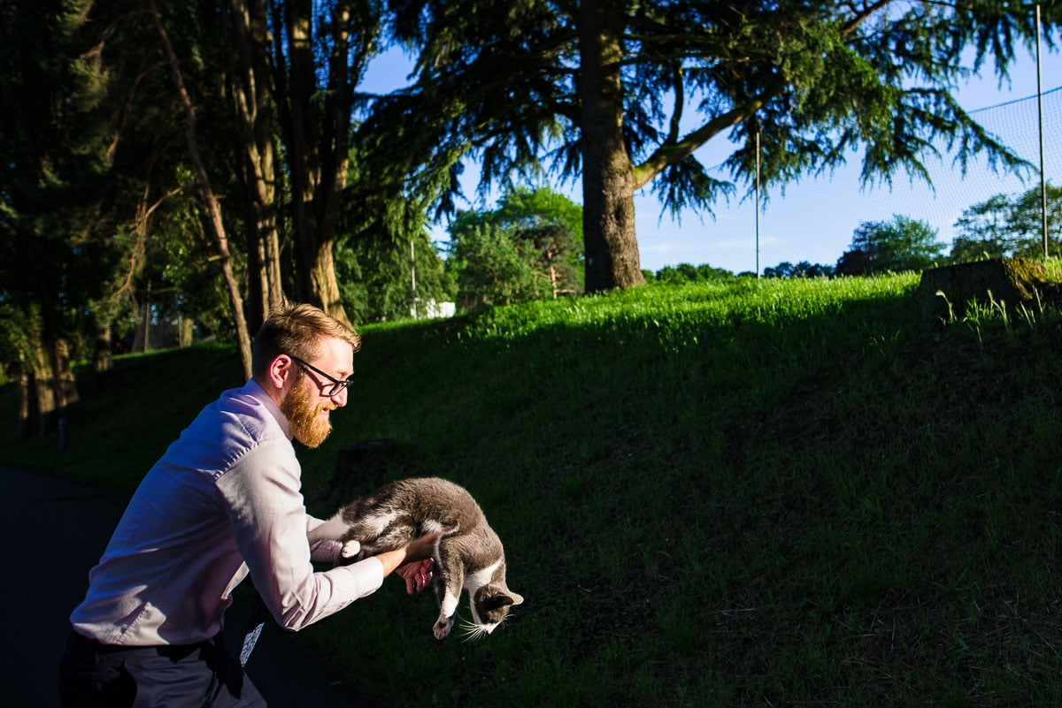 wedding guest struggles to keep cat in his grasp