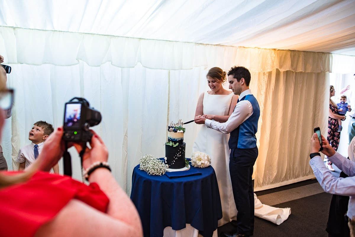 Reportage capture of the bride and groom cutting the wedding cake inside their marquee
