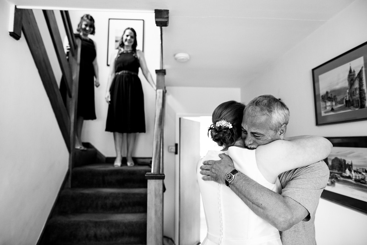 bridesmaids watch bride and father's emotional embrace at home before wedding
