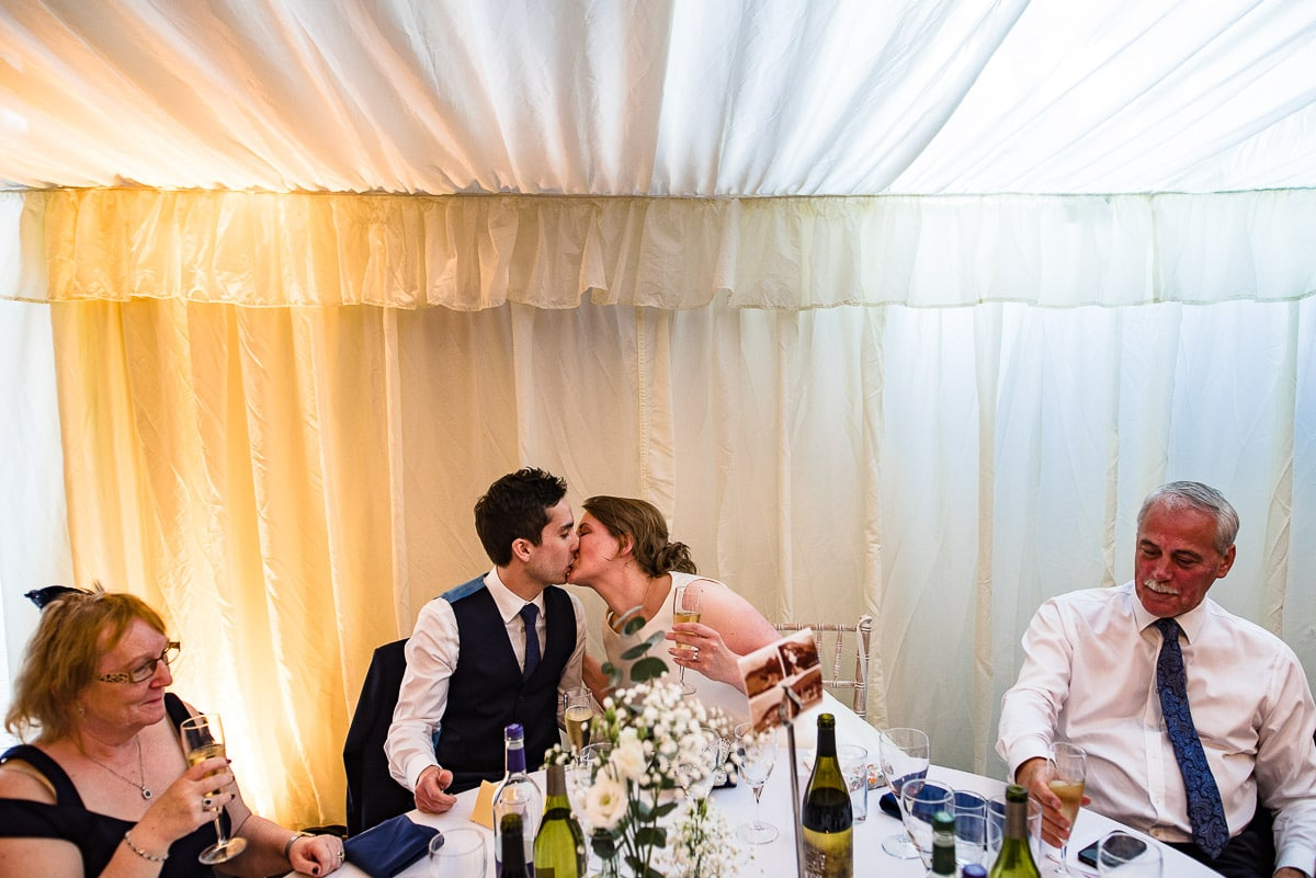 bride and groom kiss at top table during wedding breakfast