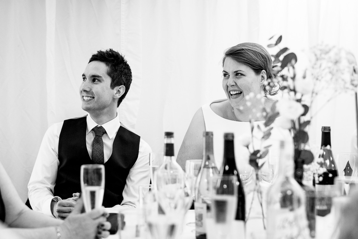 Black and white bride and groom laugh at heart felt speeches