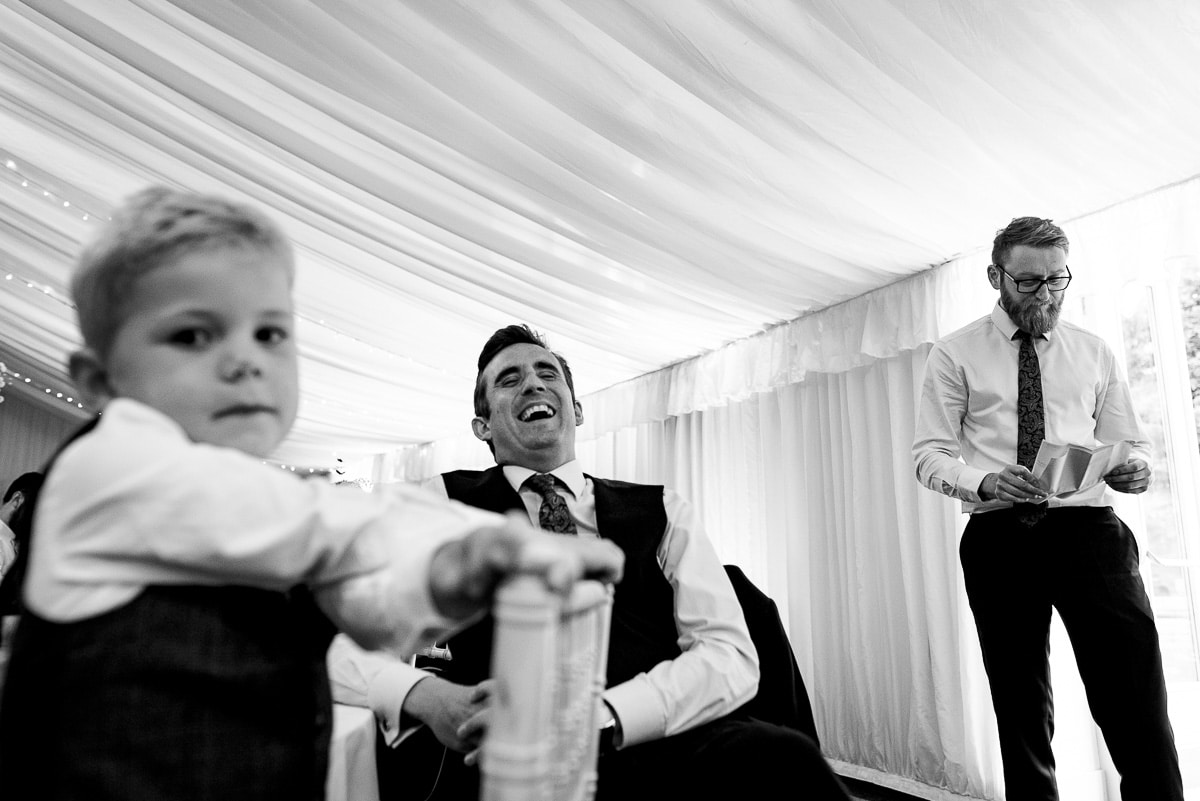 candid image of guests laughing during the wedding speeches