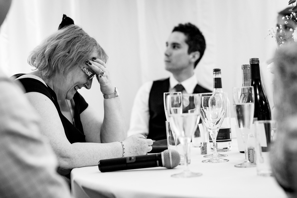 wedding guest holds her head in hands at speeches