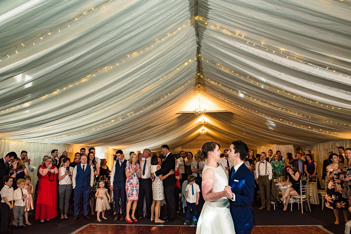 bride and groom have first dance as guests gather around to watch inside marquee