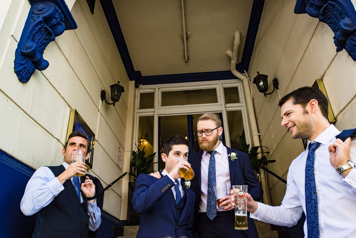 groom and guests in blue ties drinking pints before the wedding