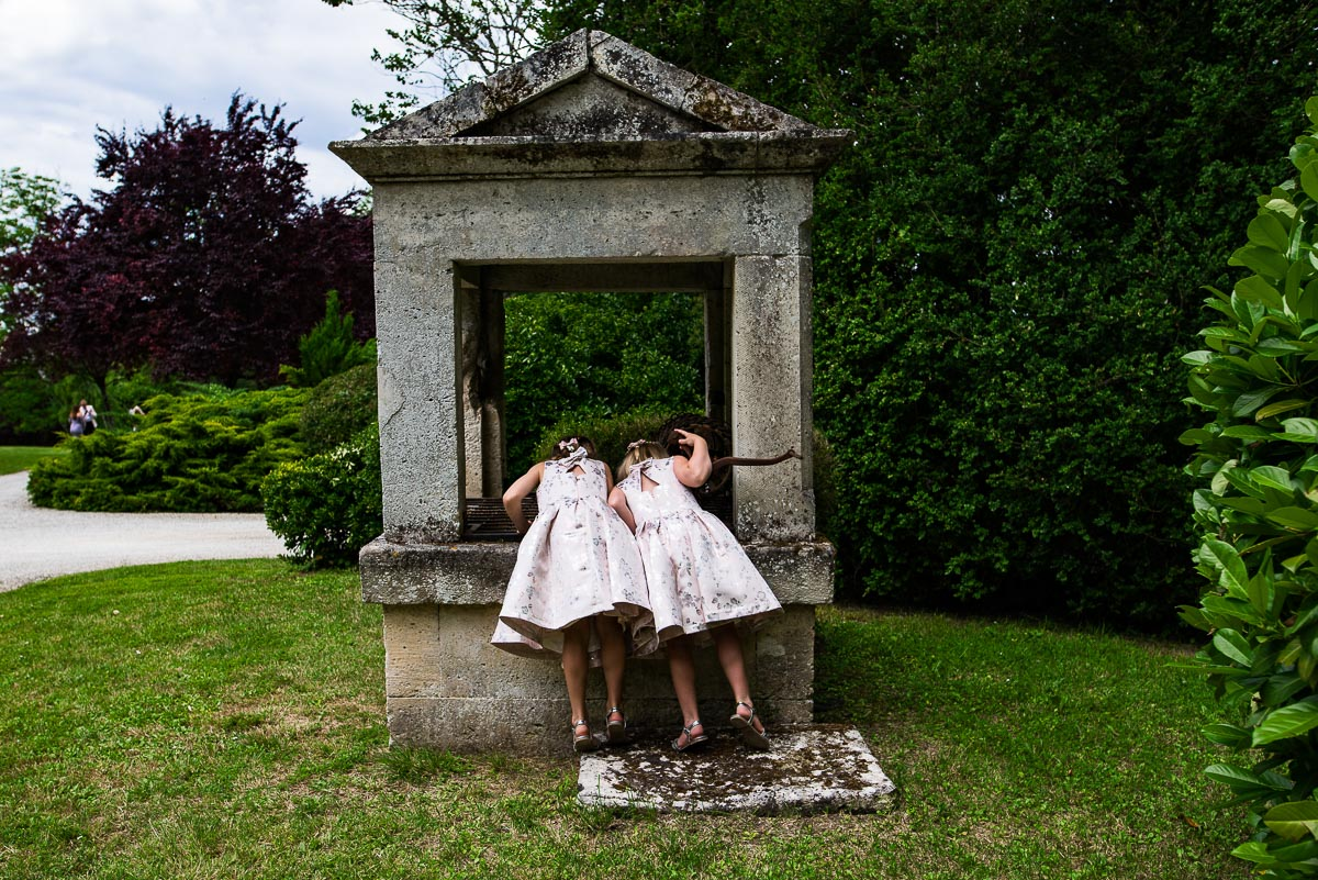 Flower girls looking down the well at Chateau La Guaterie France