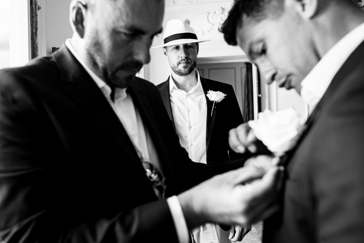 Groomsmen fixing buttonholes at Chateau La Guaterie wedding photos