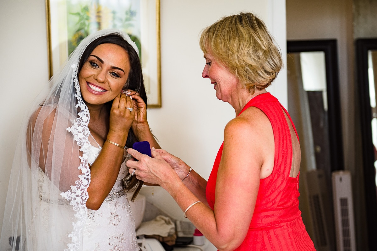 bride smiling and fixing her earrings with mother at Chateau La Guaterie