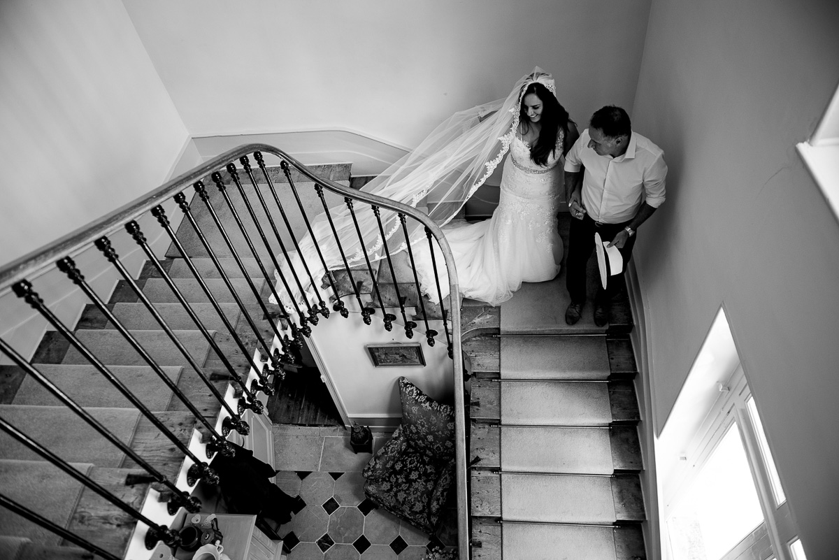 Father of the bride walks bride down Chateau La Guaterie staircase
