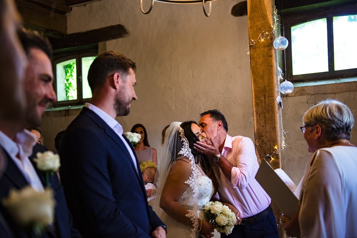 Wedding ceremony father of the bride kissing daughter at Chateau La Guaterie France