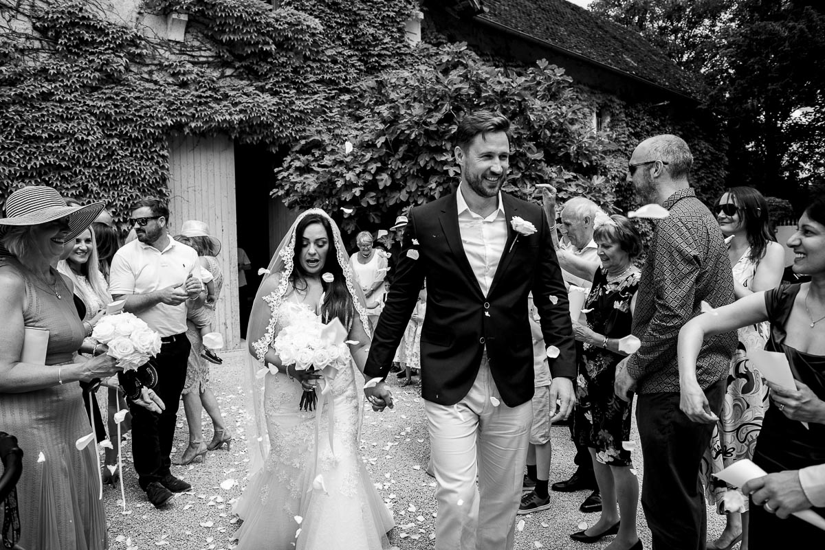 Throwing confetti at bride and groom Chateau La Guaterie France
