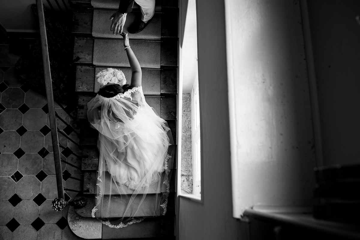 Emotive image of bride and groom on staircase at French Chateau