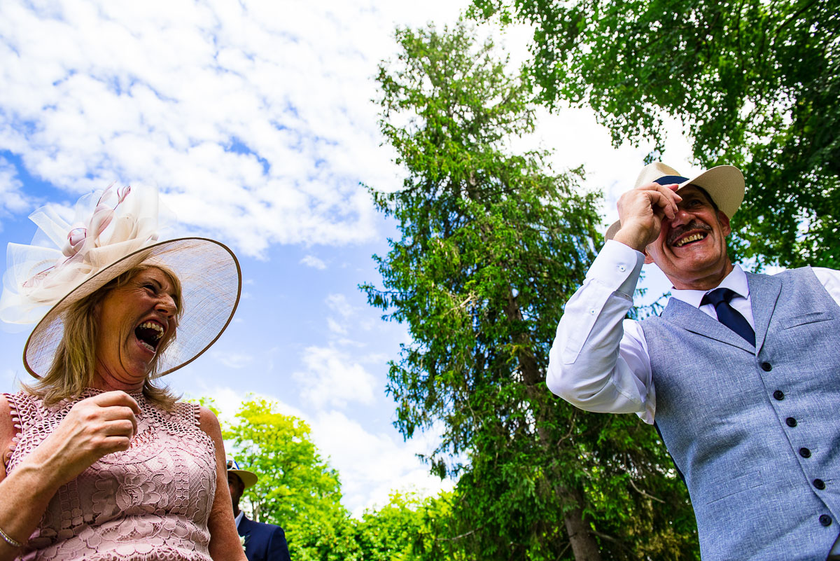 Wedding guests laughing and wearing hats outside