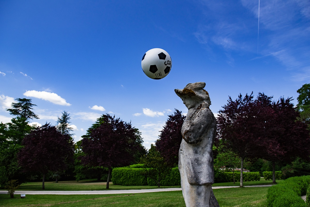 Statue at Chateau La Guaterie with football in mid-air