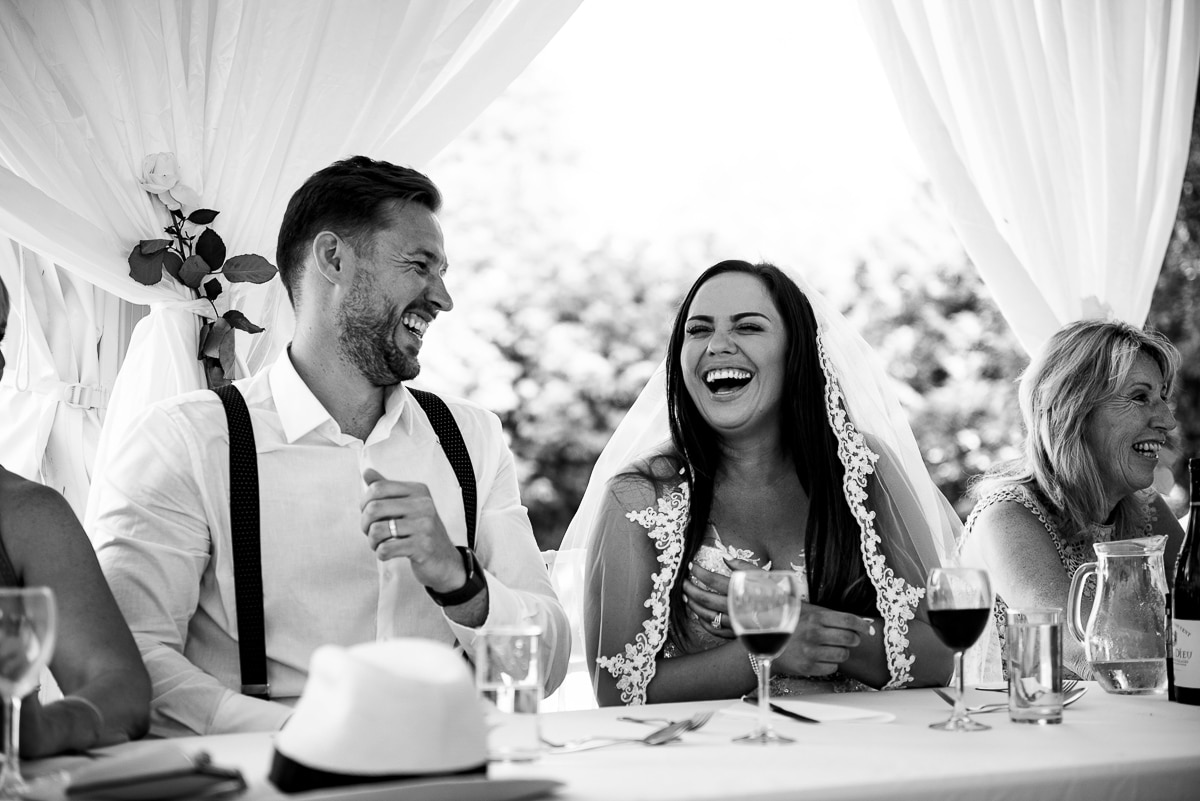 Bride and groom laughing at top table during wedding breakfast