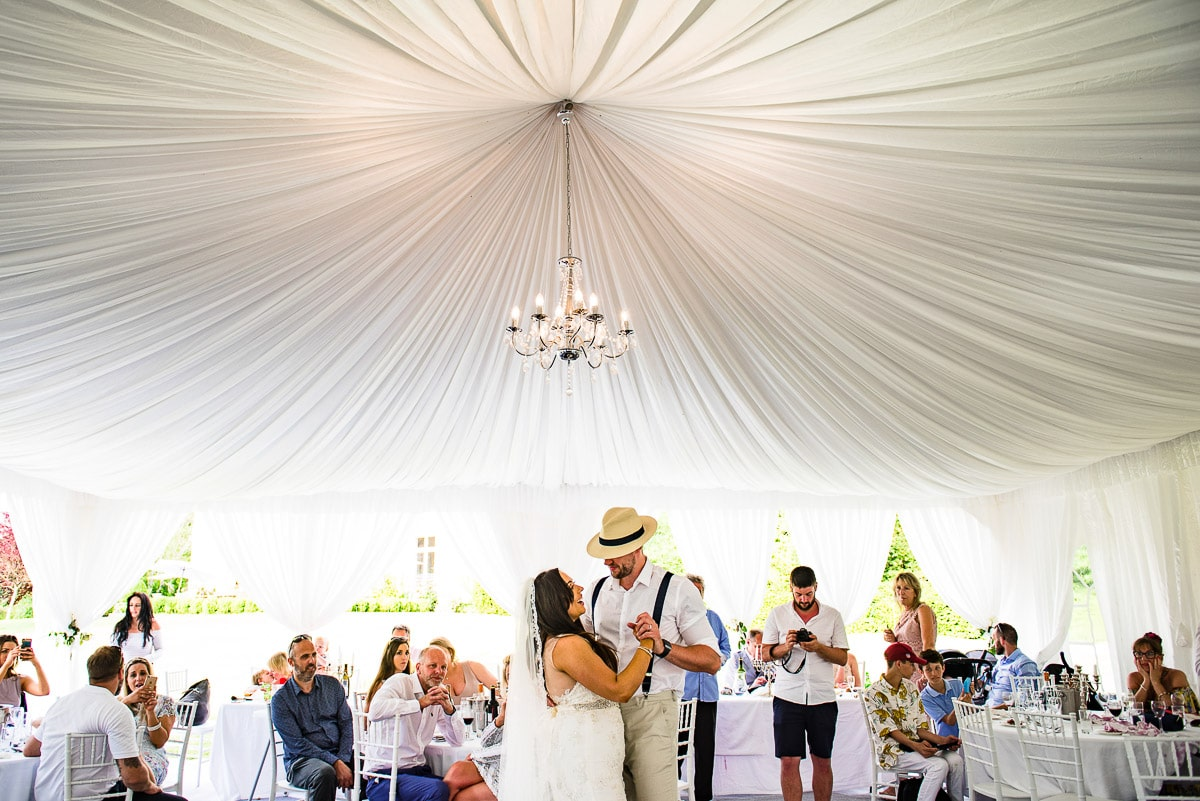 Guests watch bride and groom first dance inside marquee Chateau La Guaterie Dordogne