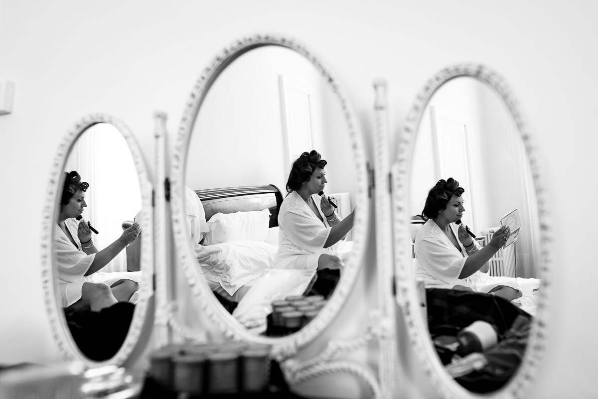 Bride applying make up in mirror reflections Chateau La Guaterie
