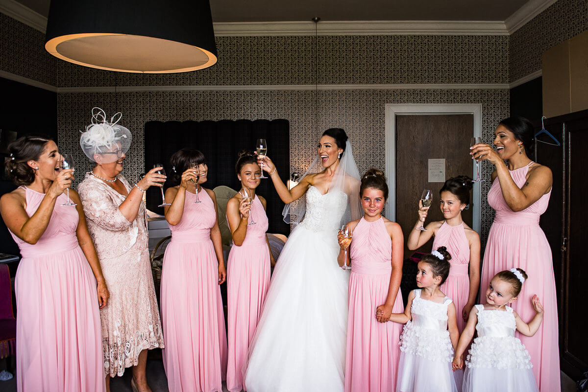 bride and bridesmaids toast champagne in their dresses from Lisa rose bridal
