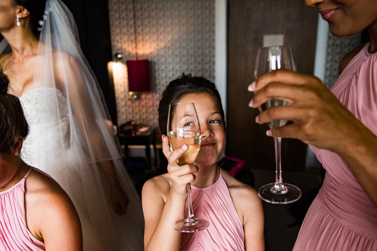 young bridesmaid peering through wine glass