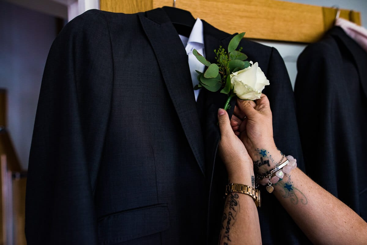 Attaching white rose buttonhole to wedding suit detail