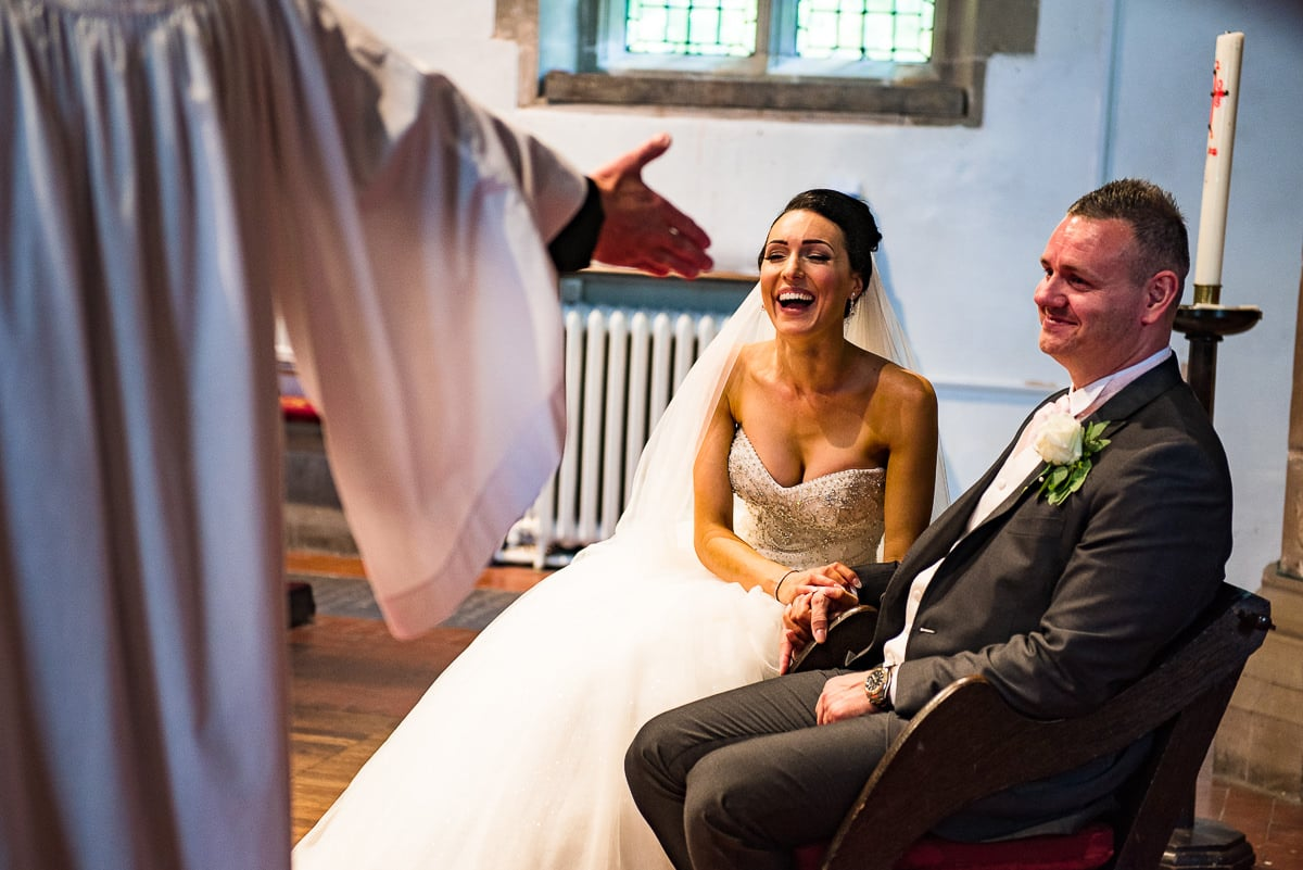 bride and groom giggle as vicar conducts their wedding ceremony