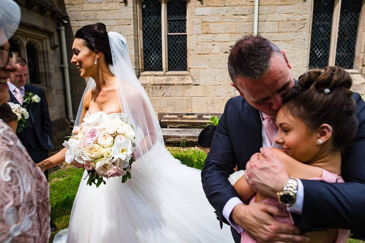 bride chats with guests outside church whilst groom hugs daughter