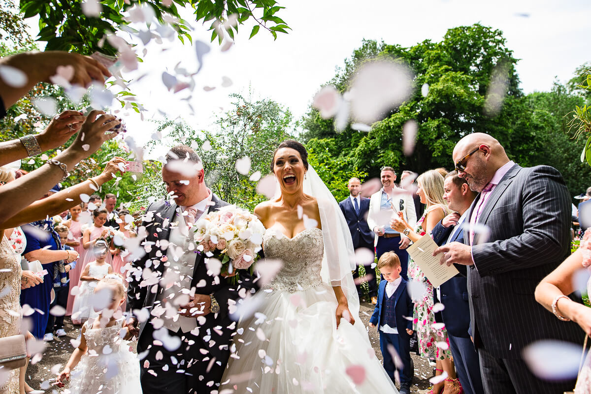 guests throw petals onto the newly married couple outside Hampton Church