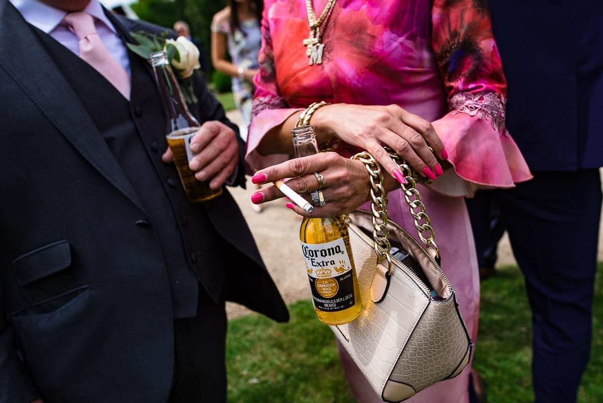brightly dressed wedding guest with cigarette and beer bottle