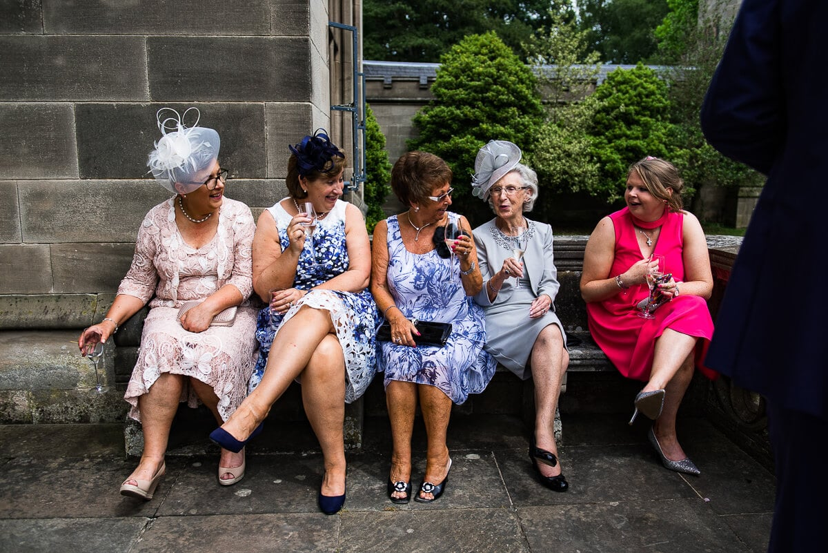 ladies in their wedding colourful outfits gossip out side hampton manor