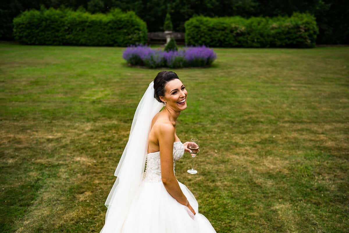 bride enjoys champagne and a laugh in gardens of Hampton manor