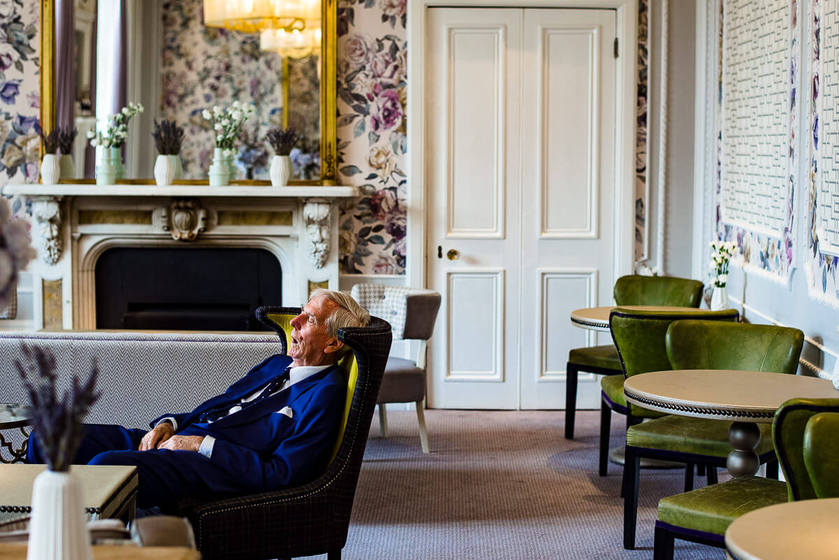 elderly wedding guest asleep in Hampton manor dining room