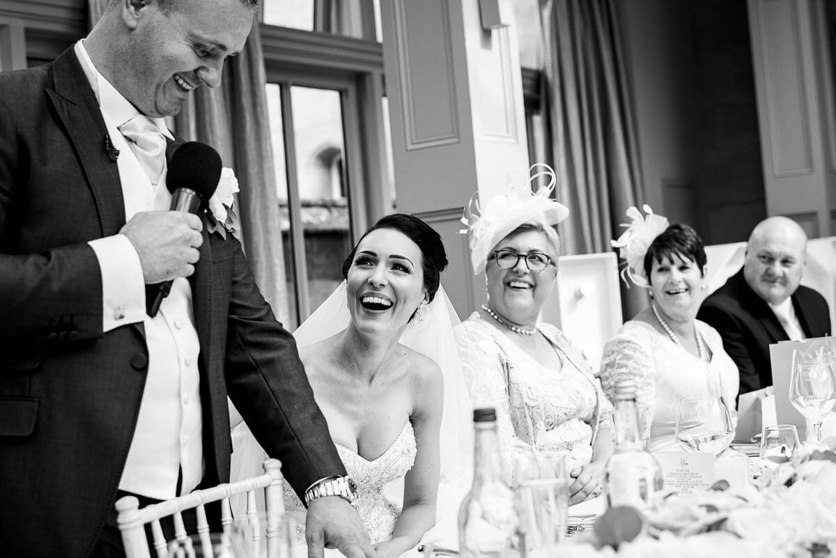 bride and family laughing at grooms wedding speech