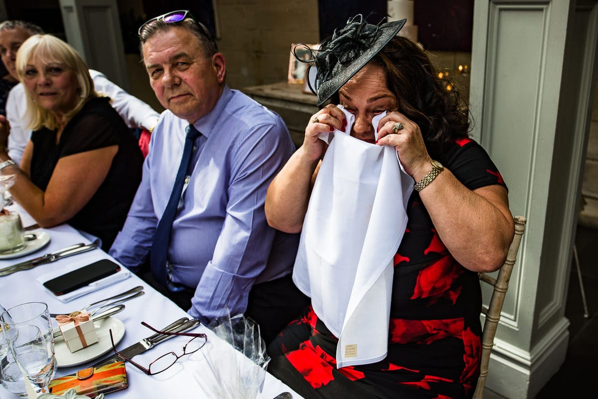 wedding guest wipes away tears of laughter with napkin