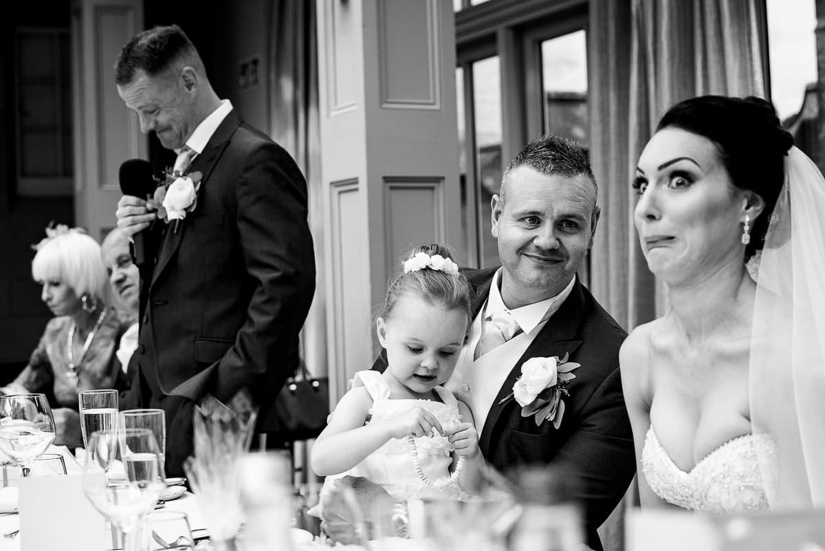 bride pulls faces as best man reads his speech