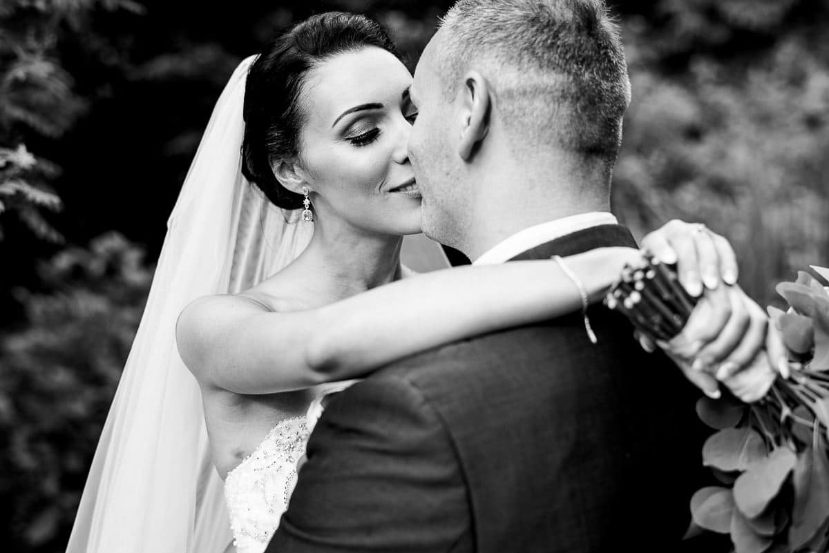Romantic black and white portrait of bride and groom kissing