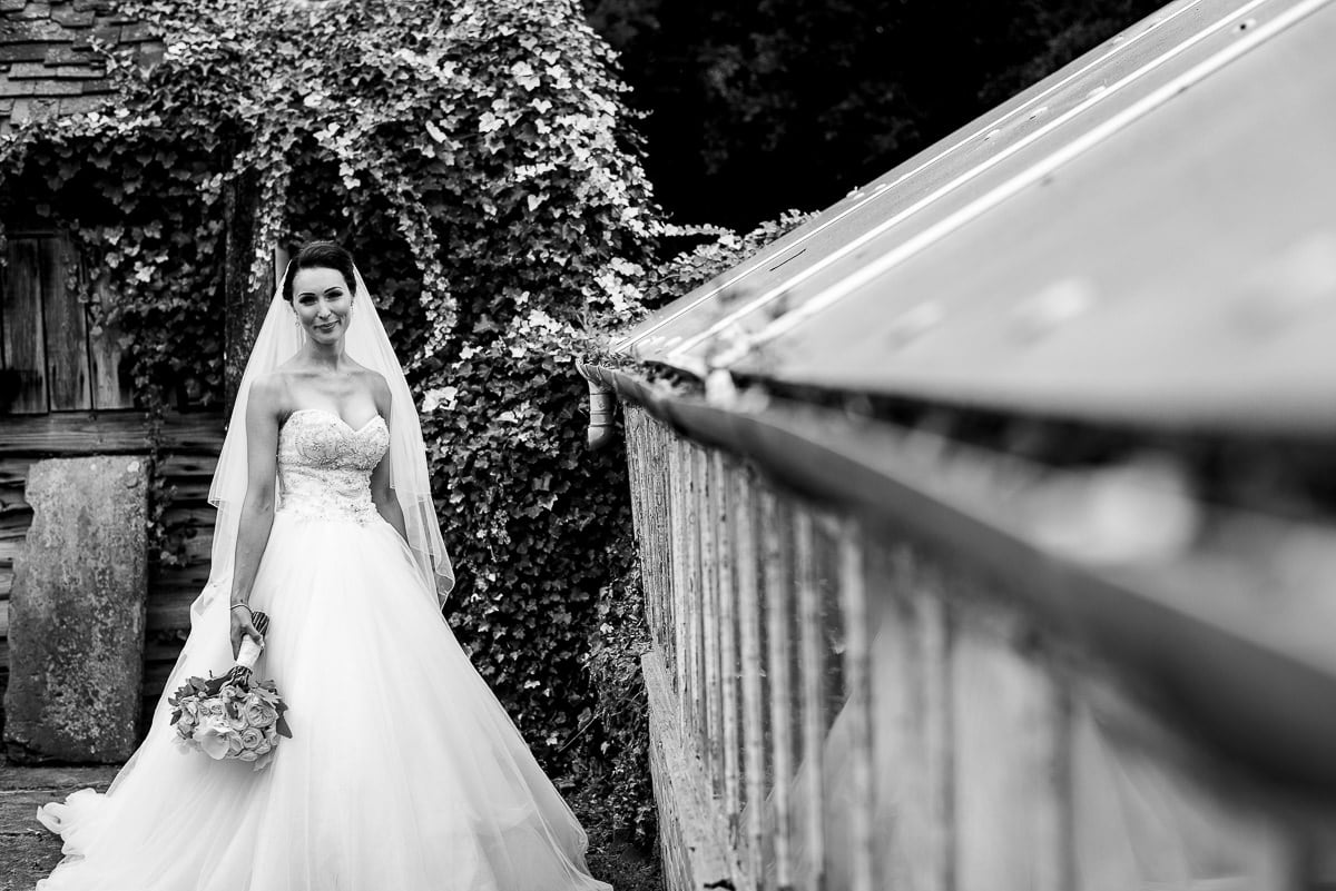 bride poses in her glamorous Sophia Tolli wedding dress with bouquet